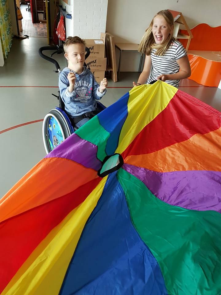 Jongen in rolstoel en meisje spelen samen met gekleurd laken