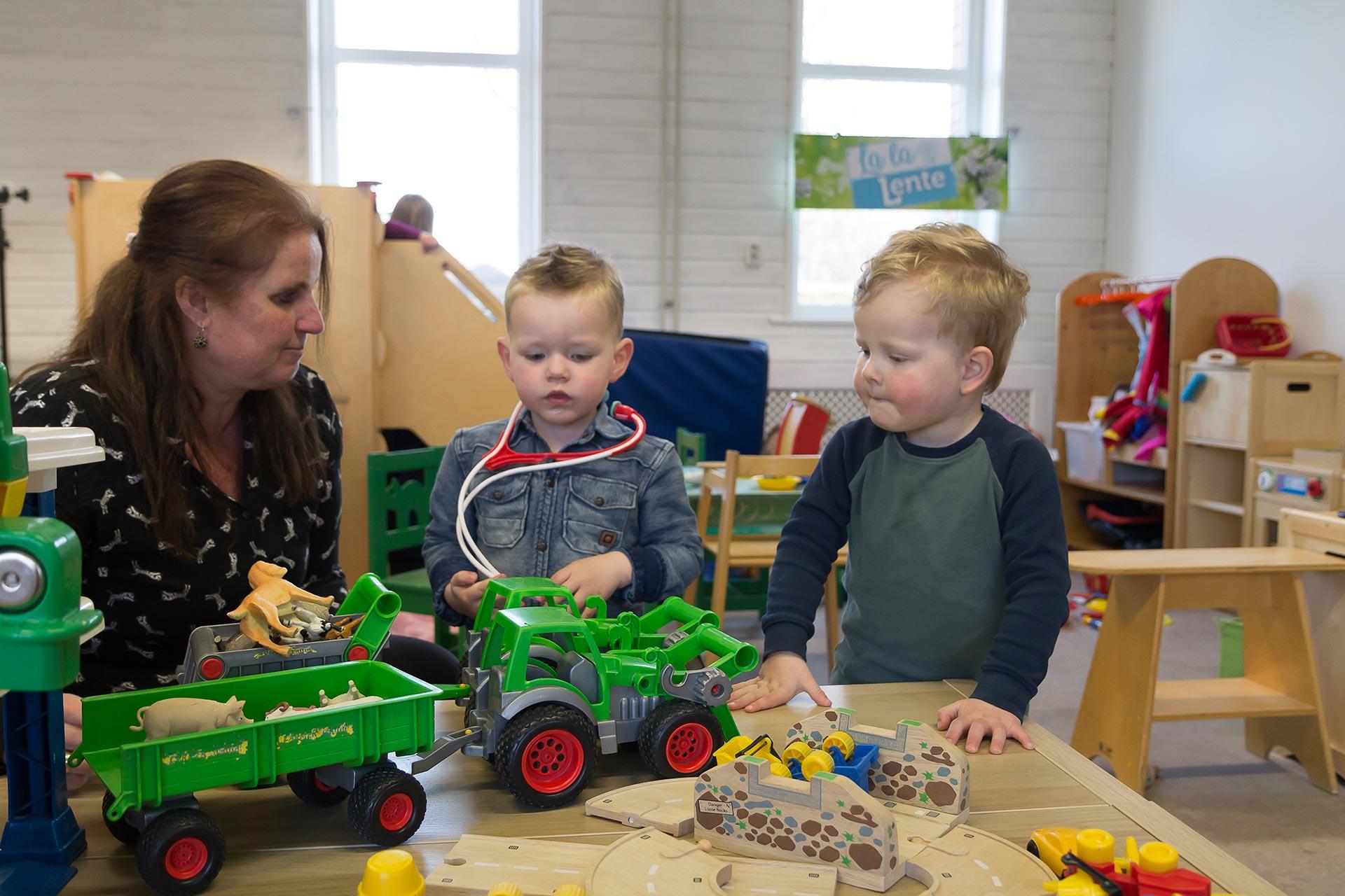 Juf en twee kinderen met speelgoed bij tafel