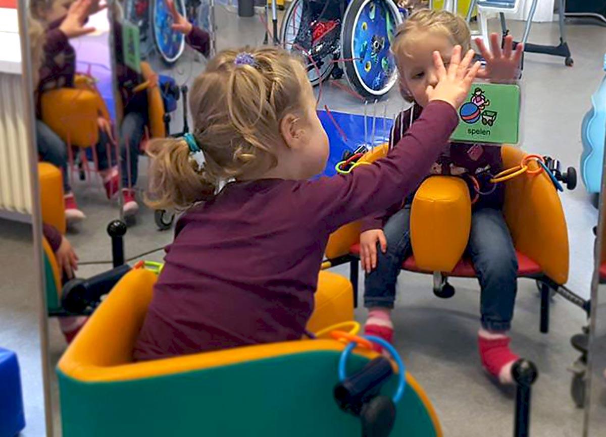 Kind in aangepaste stoel leert op school