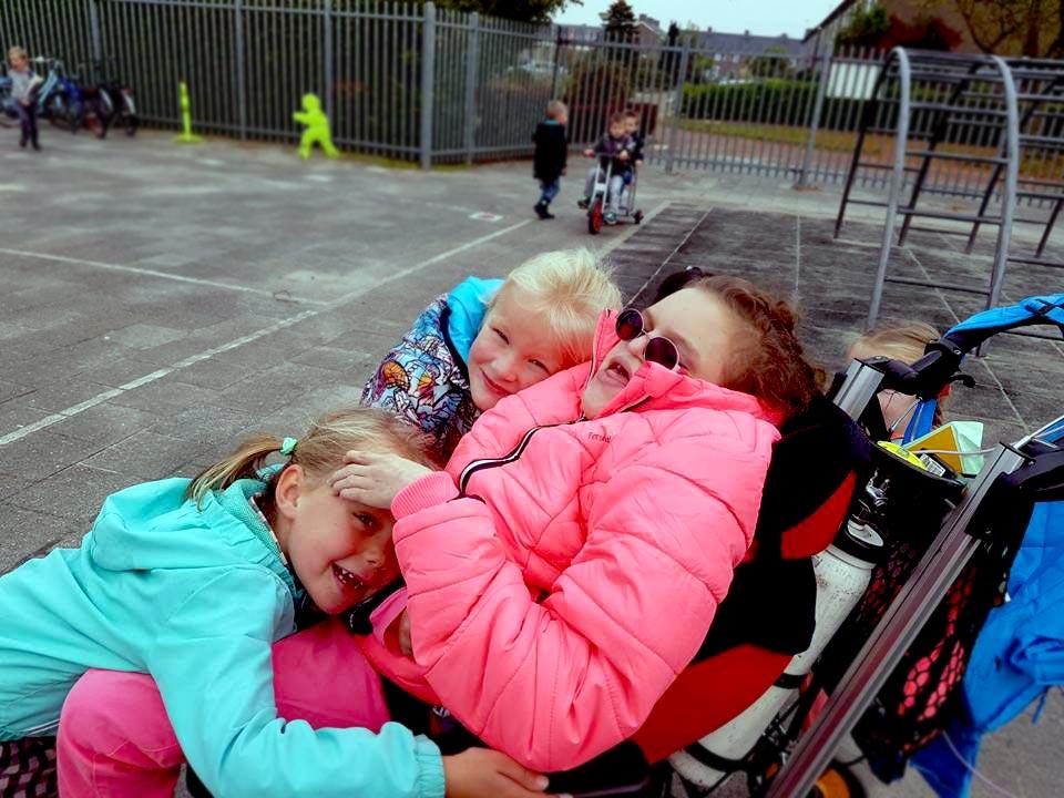 Kinderen knuffelen kind met meervoudige beperking in rolstoel op schoolplein