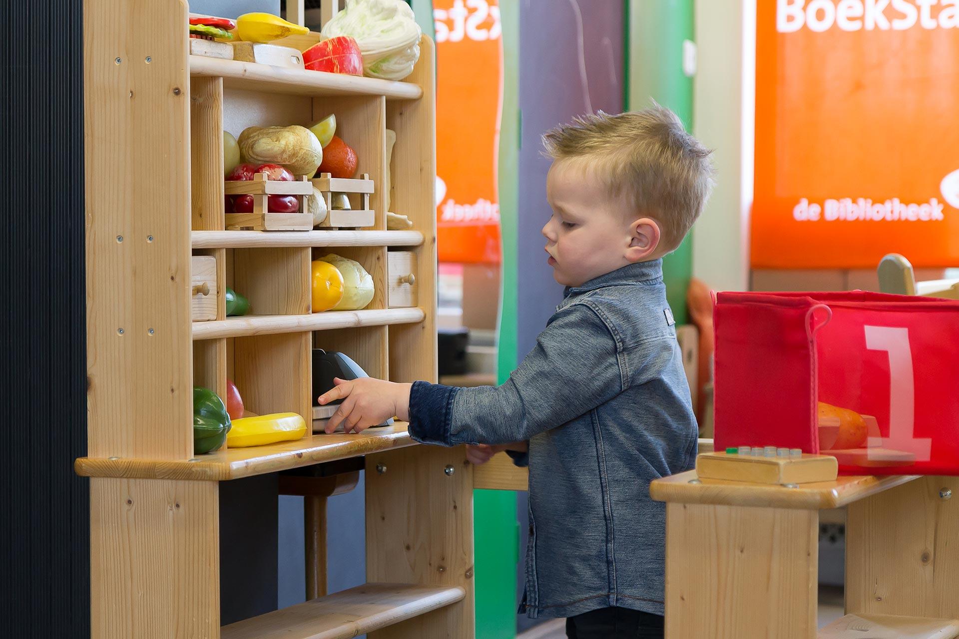 Peuter speelt winkeltje in de thema speelhoek