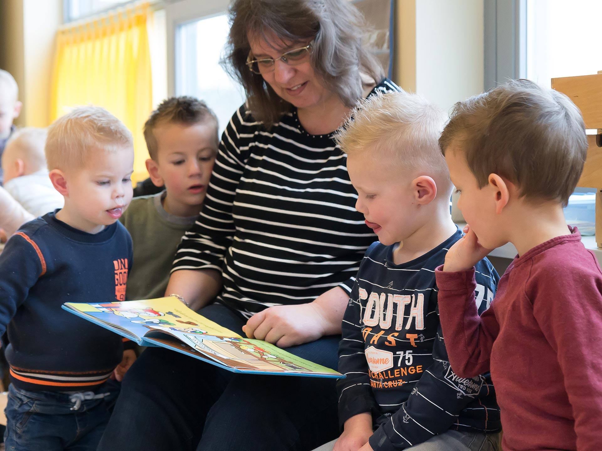 Foto van kinderen die worden voorgelezen op de peuterspeelzaal